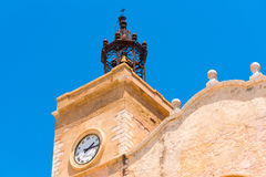View of the church tower with clock in Sitges, Barcelona, Catalunya, Spain.  on blue background. Stock Photos