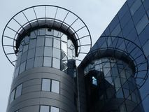 Glass office building parapet detail and design feature. View of circular office building tower and parapet and design features in glass curtain Royalty Free Stock Photos