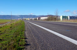 View of the city. Asphalt road, field and housing estate royalty free stock photo