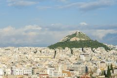 View of the city of Athens, and a large mountain with a monastery on top. Beautiful blue sky stock image