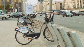 View of city bike station near road busy with traffic. Slow motion view. View of city bike station near road busy with traffic. Slow motion stock footage