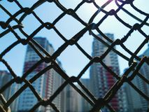 A view of the city houses behind the mesh fence Stock Image