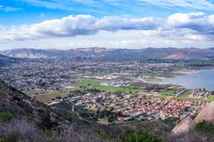 View on the city of Lake Elsinore, Southern California USA. Residential houses in a valley by the lake with mountains on the background. Panoramic view on the royalty free stock image