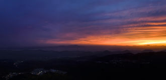 View of city lights from mountain top during sunset Royalty Free Stock Photos