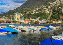 View in the city of Lugano in Switzerland. Boats at a pier on Lake Lugano, buildings on the foot of the Monte Bre mountain in the background. Lugano is the Royalty Free Stock Images
