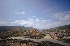 View of the city of Mtskheta and the Kura River. With feather clouds on a blue sky Royalty Free Stock Image