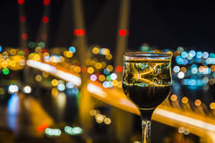 View the city at night, the bridge across the Bay at night, glasses through whic. Beautiful night scenery, goblets with drink stand in the background of the city Stock Photos