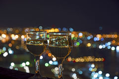 View the city at night, the bridge across the Bay at night, glasses through whic. Beautiful night scenery, goblets with drink stand in the background of the city Royalty Free Stock Images
