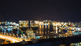 View the city at night, the bridge across the Bay at night, glasses through whic. Beautiful night scenery, goblets with drink stand in the background of the city Stock Photography
