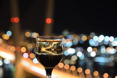 View the city at night, the bridge across the Bay at night, glasses through whic. Beautiful night scenery, goblets with drink stand in the background of the city Royalty Free Stock Photography