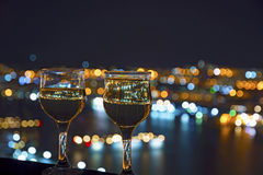 View the city at night, the bridge across the Bay at night, glasses through whic. Beautiful night scenery, goblets with drink stand in the background of the city Royalty Free Stock Photo