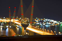 View the city at night, the bridge across the Bay at night, glasses through whic. Beautiful night scenery, goblets with drink stand in the background of the city Stock Images
