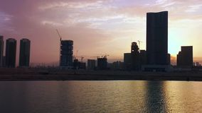 View of a city`s modern skyscrapers and work district around a waterfront at sunset - Al Reem Island, Abu Dhabi.  stock video footage