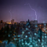 View of city storm through wet window with blurred rain drops Stock Photography