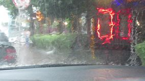 View of the city street in a thunderstorm and heavy rain through the windshield of the car. Blurry advertising lights. The red car light flashes. Abstract blur stock footage