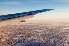 View of City on Sunrise Outside Airplane Window Stock Image