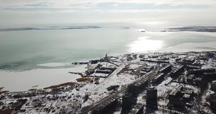 View from the city to the freezing lake. Shooting from a drone from a height. Open frames of low houses, snow, ice lake and the sky with clouds. The same type stock video footage
