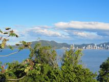 View from city to seaside, with forest in the foreground. Coastal city landscape with forest in the foreground, late afternoon in blue sea Stock Image