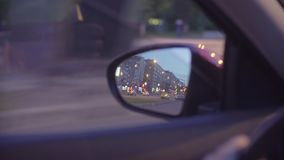 View of the city traffic in car`s rearview mirror. Point of View of the city traffic in car`s rearview mirror and side window. Defocused city lights. Moscow stock footage
