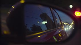 View of the city traffic in car`s rearview mirror. Point of View of the city traffic in car`s rearview mirror and side window. Defocused city lights. Moscow stock video footage