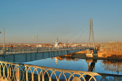 View of the cityTyumen . Russia. Embankment  of river Turа and suspended cable-stayed pedestrian bridge, called the bridge of lovers in the rays of the rising Stock Photo