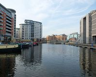 View of clarence dock in leeds looking towards the lock and river with canal boats moored alongside apartment buildings and. A view of clarence dock in leeds royalty free stock images