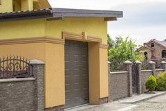 View from the clean paved street of detached garage with big aut. Omatic door, new residential cottage with balcony behind brown brick forged fence. Real estate Royalty Free Stock Image