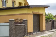 View from the clean paved street of detached garage with big aut. Omatic door, new residential cottage with balcony behind brown brick forged fence. Real estate Royalty Free Stock Photos