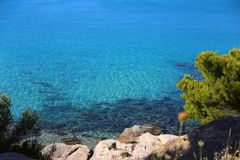 View of the clear azure water and stones with green coniferous trees. Sithonia, Halkidiki, Greece. royalty free stock photography