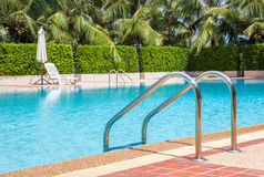 A view of clear blue swimming pool with steel ladder Stock Images