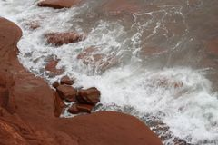View From The Cliff. Looking down from the cliff at The East Point Lighthouse to the ocean waters pounding against the red rocks. PEI, Canada Royalty Free Stock Photography