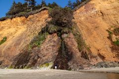 Lonely boy standing next to a small waterfall at beach on Oregon coast royalty free stock image