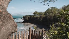 View from cliff shore with wooden fence, trees and bushes to sandy beach. Shot with Sony a7s on slider on sunny day with blue sky stock video footage