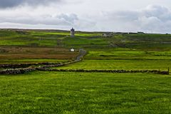View at Cliffs of Moher with guard tower from Doolin, Ireland. View over the grassland at Cliffs of Moher from Doolin, old guard tower and stone boundaries stock images