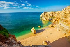 View from the cliffs over the emblematic golden beach of Praia M. Arinha and the calm ocean, in Lagoa Municipality, Algarve Stock Images