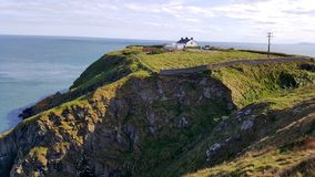 View from cliffs to the sea with house in the background Royalty Free Stock Photography