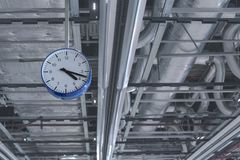 View of the clock that hangs from the ceiling against the background of ventilation pipes. stock image