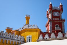 The clock tower and the curtain walls of Pena Palace. Sintra.. The view of Clock tower and the curtain walls with decorative battlements. Pena Palace. Sintra Royalty Free Stock Photo