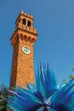 View of clock tower made of bricks and a star shape glass sculpture at Murano. Stock Photography
