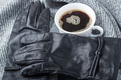 View close-up on black women`s gloves and coffee cup Royalty Free Stock Photo