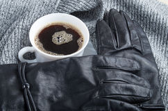 View close-up on black women`s gloves and a white coffee cup Stock Photo