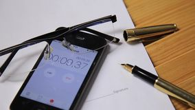 View of close up clock and stopwatch on a smartphone. man starts a stopwatch. glasses and fountain pen lie on the. Business documents stock video footage
