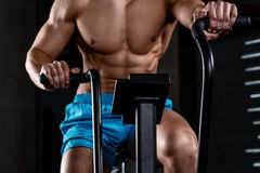 View close-up part of young man in sports shorts cycling at gym. Intense cardio workout. View close-up part of young man in sports shorts cycling at gym Royalty Free Stock Photo