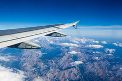 View of clouds and Rocky Mountains outside airplane window Royalty Free Stock Photo