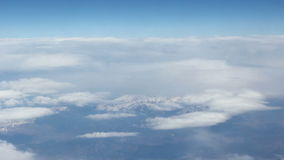 View from the clouds to the snow-capped mountains. Shooting from very high altitude. Beautiful blue sky. stock footage