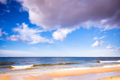 View of cloudy sky at sea with footprints on a beach Royalty Free Stock Images