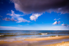 View of cloudy sky at sea with footprints on a beach Royalty Free Stock Photography