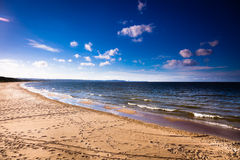 View of cloudy sky at sea with footprints on a beach Stock Photos