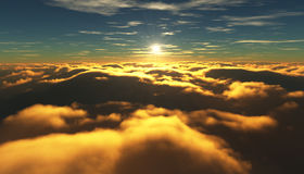 View of a cloudy sunrise while flying above the clouds. Royalty Free Stock Photos