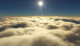 View of a cloudy sunrise while flying above the clouds. Royalty Free Stock Images